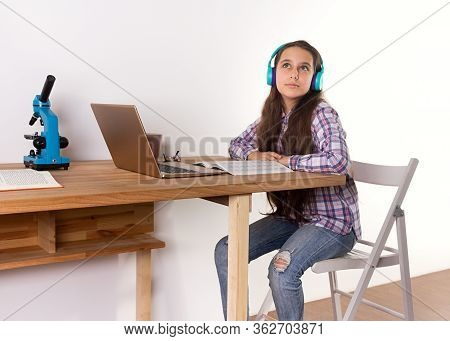 Distance Learning.home Schooling, Young Teen Girl Studying At A Laptop, Listening To Music With Head