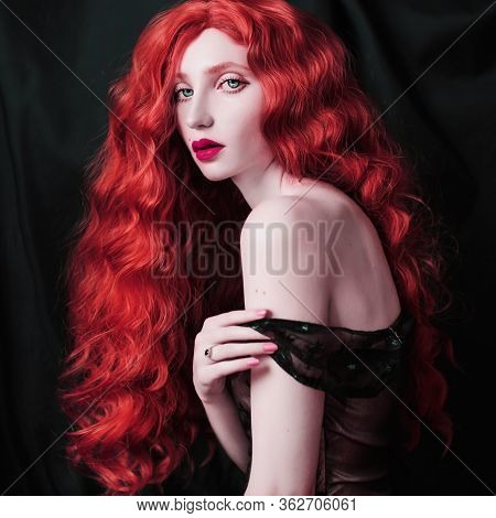 Beauty Portrait. Beautiful Fairytale Girl With Curly Red Hair In Black Dress On Dark Background. Bea