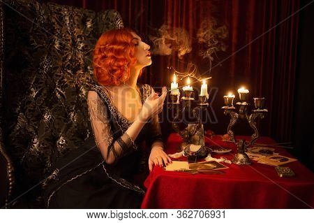 Retro Woman With Red Hair In Black Vintage Dress. Vintage Redhead Woman With Red Lips Smoking Cigare