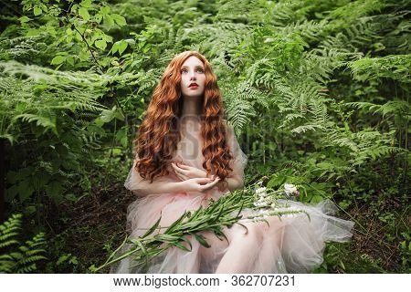 Beautiful Renaissance Girl With Curly Red Hair With A Flying Tulle Dress On The Background Of A Fern