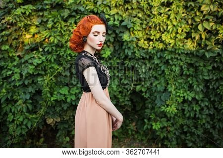 Redhead Girl In Free Flying Dress And Retro Hairstyle Against A Summer Park Background. Retro Style.