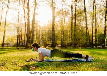 Woman With Mask Meditating/practicing Yoga In Nature Alone.social Distancing And Active Healthy Life