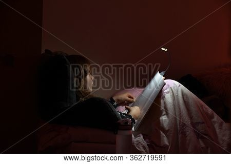 Girl Reading A Book In Bed At Night In Comfy Bedroom Wearing Pyjamas