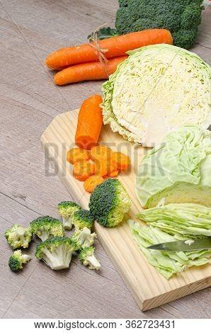 Fresh Green Broccoli, Carrot, Garlic, Onion And Cabbage On A Wooden Cutting Board. Macro Photo Green