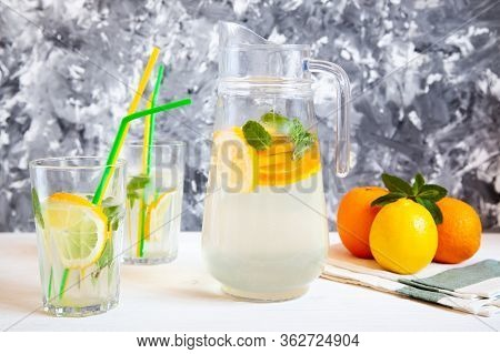 Lemonade In A Glass Jug On A White Wooden Table And Glasses With Straws.