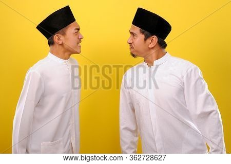 Image Of Two Young Asian Muslim Men Look Furious Each Other. Ramadan Concept. Isolated On Yellow Bac