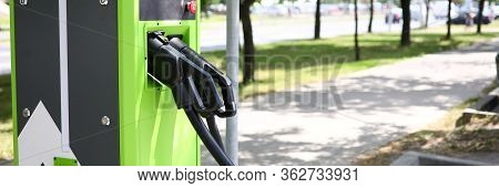 Focus On Green Power Supply For Electric Automobile. Modern Charge Gun And Pile On Road For Clean En