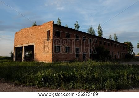 Large Abandoned Red Brick Building. Abandoned Industrial Enterprise. Trees Grow On The Roof Of An Ab