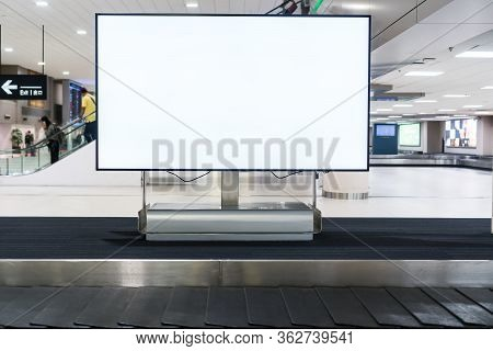 Blank Advertising Billboard At Conveyor Belt Luggage In Airportat Airport. Copy Space For Cutomer Te