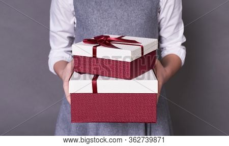 Portrait Of A Red-white Cute Gift Box, Which Is Gently And Gently Held By The Hands Of A Child Who G