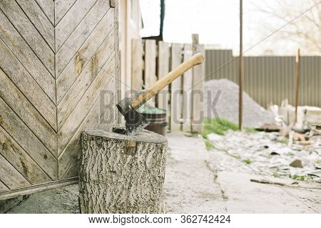 Ax Stuck In The Wooden Stump. Woodcutters Ax On The Stump.