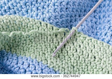 Crochet Hobby Background With Hook. Close Up. Crochet Process. Green And Blue Almost Finished Plaid.