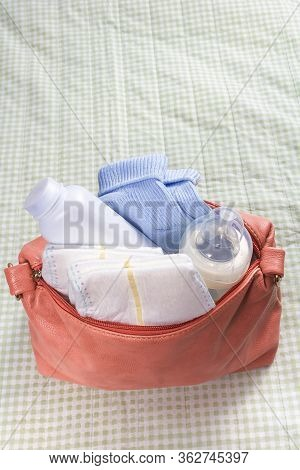 Small Pink Diaper Bag On Changing Pad. First Care Baby Accessories With Bottle. Soft Green Backgroun