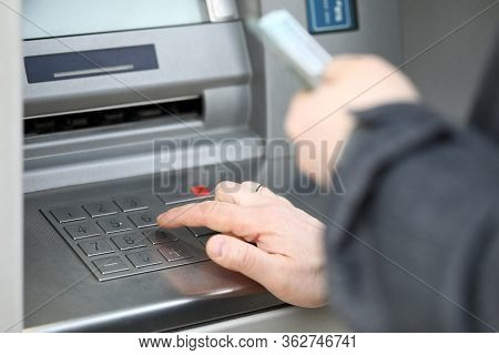 Close-up Of Man Pressing Pin Code On Cash Machine Outdoors. Person Getting Salary Or Pension. Credit