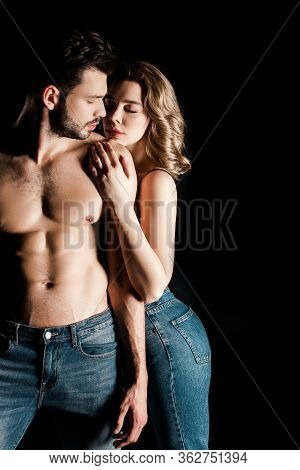 Sensual Girl Embracing Shirtless, Muscular Boyfriend Isolated On Black