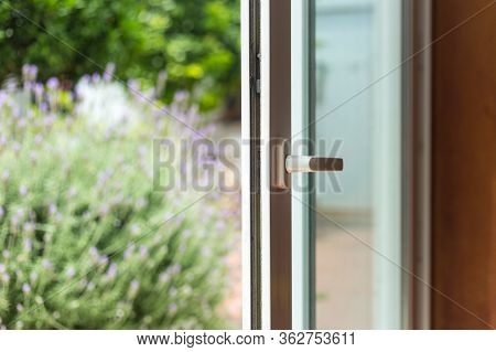 Opened Door Of A Family Home. Lock Of The Sliding Door With The Yard Of Background. White Pvc Door A