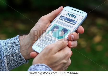 Coronavirus News. Man With Smartphone In His Hands Reading About Covid-19 Virus. Online News In The