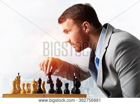 Businessman Moving Chess Figure In Chessboard. Successful Management And Leadership. Handsome Man In