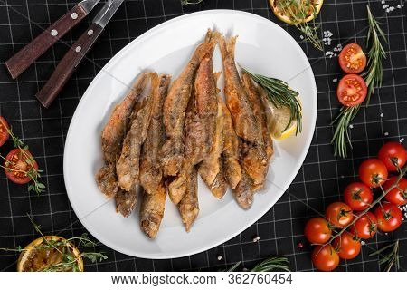 A Dish Of Fried Red Mullet. Table Setting, Decorated With Greens And Cherry Tomatoes.