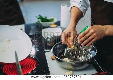 Chef Grating Cheese, Chef Hand Grating Parmesan Cheese With Grater, Chef Rubbing Cheese On A Grater,