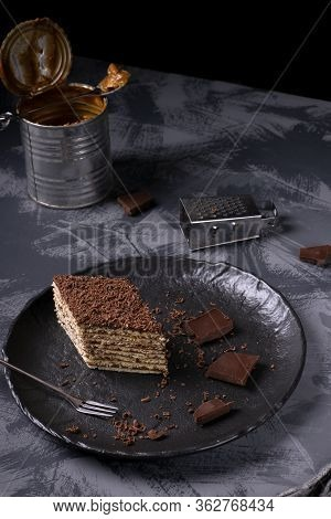 Mikado Cake With Caramel And Chocolate Buttercream On The Black Ceramic Plate. Armenian Cuisine Dess