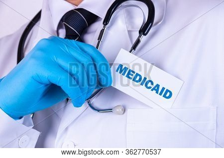 Doctor, Man Put A Card With The Text Medicaid In His Pocket. Medical Concept.