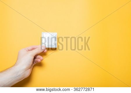 The Girl Holds A Condom In Hand. Yellow Background, Place For Text.