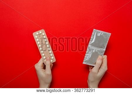 The Girl Holds Contraceptive Pills And Condoms In Her Hands. Contraception. Red Background, Place Fo