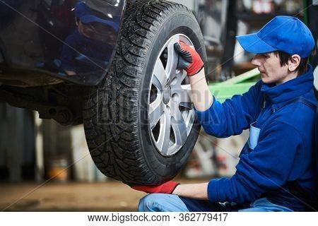 Auto service. Worker screwdriving an automobile wheel. Break maintenance or tyre replace