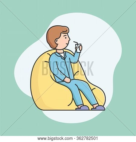Pajamas Party Concept. Young Boy Is Sitting On Padded Stool And Drink Cocktail. Smiling Man In Pajam
