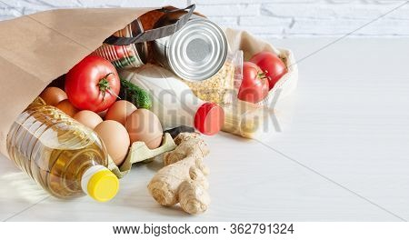 Paper Shopping Bag With Various Food On White Wooden Background. Food Donation, Safe Delivery Servic
