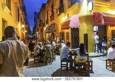 Havana, Cuba - 25 July 2018: Tourists And Locals Eating Outside A Cafe At Night With Music Being Pla