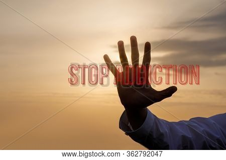 The Concept Of Stop Addiction.hand Towards The Sunset Background And The Inscription Stop Addiction.