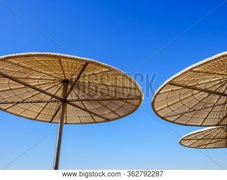 Straw Sunshade In Sunny Summer Day, Tropical Background.