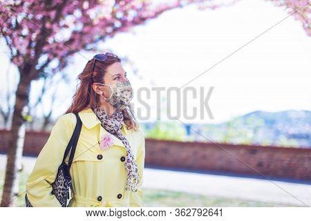 Young Woman In Mask Walking At Park During Sakura, Springtime