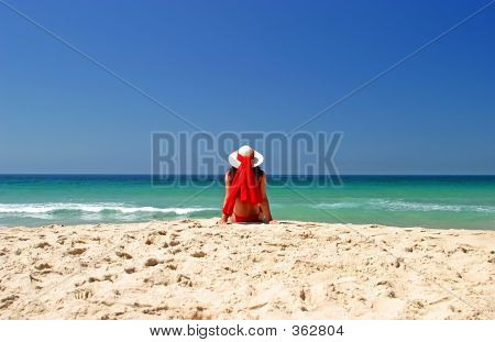 Woman In Red Bikini And Hat Sitting In Peace On A Beautiful Sunny Beach.