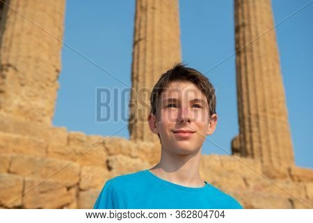 Handsome cheerful teen boy against ancient Greek Temple, Agrigento, Sicily. Famous tourist attraction in Italy. Ruins of marble columns of the Doric order. Travel destination. Tourism