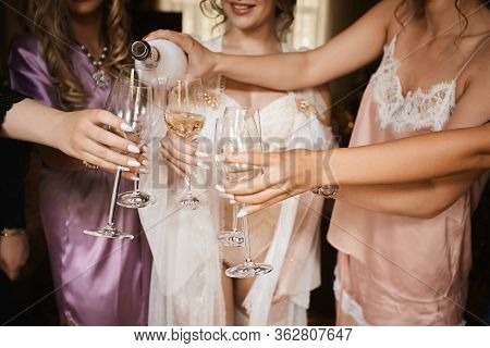 Female Hands Holding Glasses Of Champagne At Hen Party. Bride And Bridesmaids Toasting With Champagn