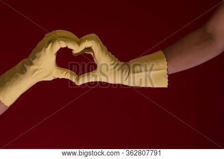 Hands With Yellow Gloves Making A Symbol Of A Heart On A Red Background. Photo With Copy Space. Love