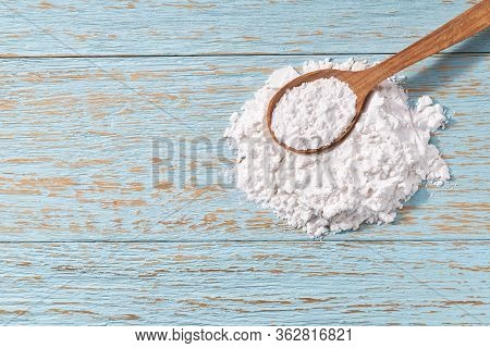 Potato Starch In A Wooden Spoon With Blue Wooden Table. Top View.