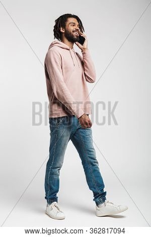 Full length portrait of a young african man wearing hoodie standing isolated over white background, talking on mobile phone