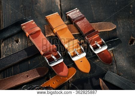 Handmade Brown Tone Watch Straps With Steel Buckle Laying On Wooden Rustic Surface Next To Leather C