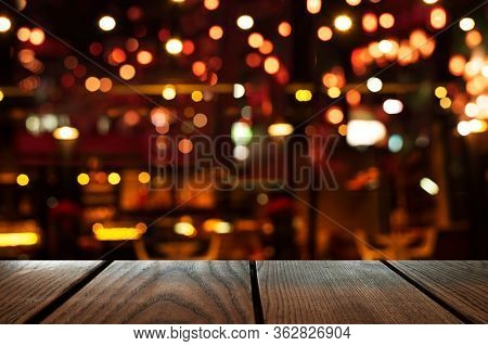 Blur Bokeh Of Bar Or Club Party Dark Night Light Background With Wood Table Background