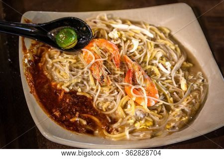 Singapore Cuisine Seafood Hokkien Mee With Jumbo Prawns, Squid, Pork And Eggs Fried Together With Ye