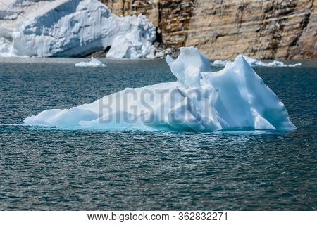 Iceberg Floats In Blue Waters Of Iceberg Lake