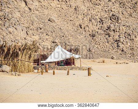 Reed Shacks Of Bedouin Village, Medium View. Rocky Mountain In Egyptian Desert. Selective Soft Focus