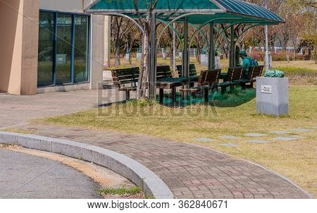 Jinan, South Korea; April 21, 2020: Unidentified Man Sitting On Covered Park Bench Checking His Phon