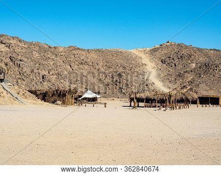 Bedouin Village In Egyptian Desert, Long View. Clear Blue Sky Over Grey Mountain. Reed Shacks Befor