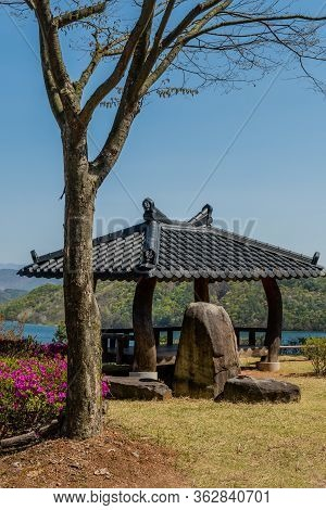 Jinan, South Korea; April 21, 2020: Pavilion With Ceramic Tiled Roof Behind Boulders And Leafless Tr