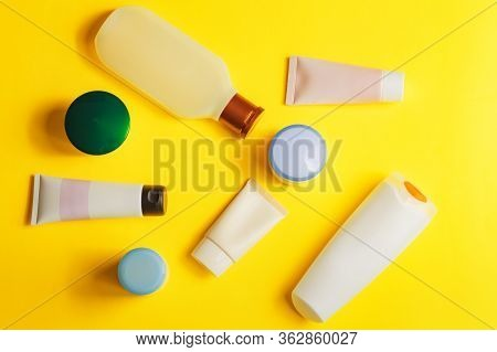 Different Colorful Beauty Toiletries On Yellow Background. Men And Women Care Products For Hair And